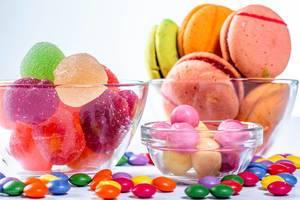 Farbige Plätzchen und Süßigkeiten auf weißem Hintergrund