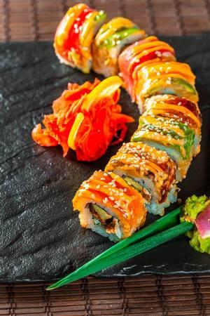 Farbiges, appetitlich angerichtetes Sushi mit Lachs auf schwarzer Steinplatte