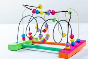 Farbiges Kinderspielzeug mit Kugeln in Labyrinth fördert Feinmotorik und logisches Denken