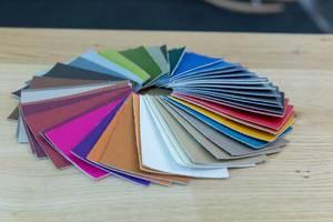 Farbmuster aus Stoff liegen in Kreis auf Holztisch