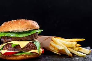 Fast food concept-French fries and hamburger on black background (Flip 2019)