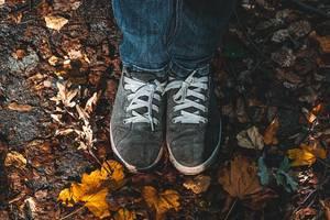 Feet in shoes on fallen dry leaves