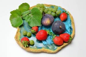 Feigen mit Erdbeerenund Weintrauben geschückt mit Weinblättern auf blauem Tonteller