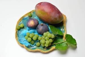 Feigen mit Mango und Weintrauben auf blauem Tonteller mit Weinblättern geschmückt
