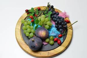 Feigen mit weißen und schwarzen Weintrauben und Hagebutten auf Schieferplatte mit blauem und rosafarbigem Netz