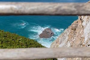 Felsen im türkisblauen Ozean vor der Küste von Cabo da Roca mit Essbarer Mittagsblume im Vordergrund