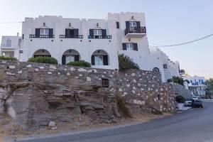 Felsen und Mauer vor einem griechischen Wohnhaus aus weißem Kalkstein, auf der Mittemeerinsel Paros