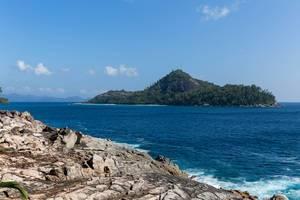 Felsenküste auf Mahé, nahe Anse des Anglais mit Blick auf die Seychellen-Insel Thérèse im Indischen Ozean