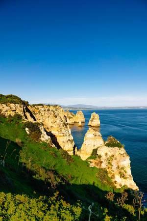 Felsige Küste mit steilen Klippen und blauem Meer bei Lagos, Portugal