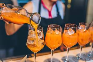 Female bartender pours orange-coloured drink in glasses filled with ice