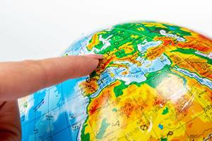 Female finger pointing to Europe on the globe