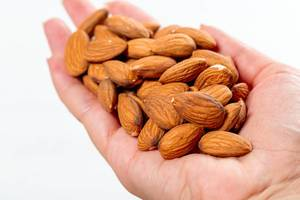 Female hand full of almonds nuts on white background (Flip 2019)