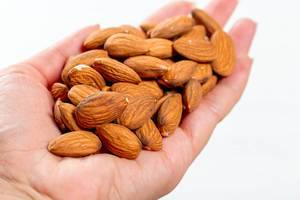 Female hand full of almonds nuts on white background