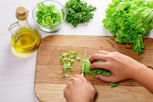 Female hands slicing the lettuce. The concept of cooking healthy food (Flip 2019)
