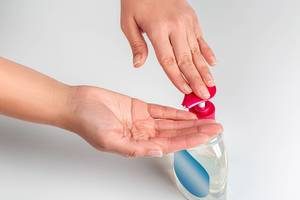 Female hands use antiseptic soap for hand disinfection