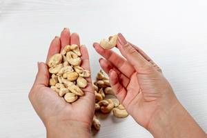 Female hands with cashew nuts. Healthy food concept (Flip 2019)