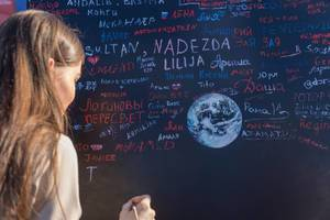 Female soccer fan writing on black board with paint brush