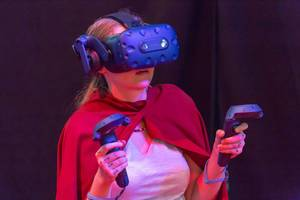 Female visitor with cape gaming with VR headset and controllers