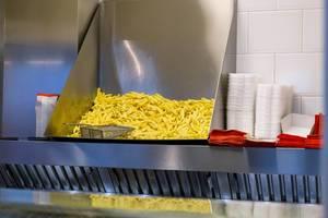 Fertige Pommes Frites in Restaurantküche neben Pappschalen bereit zum Verkauf
