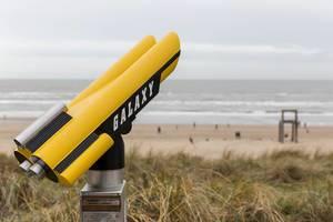 Fest installiertes Fernglas für den Blick über den Sandstrand von Zandvoort und den übergroßen Stuhl