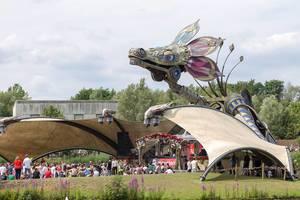 Festivalbesucher von Tomorrowland chillen beim Rose Garden Stage mit einem riesigen metallischen Drachen über ihnen
