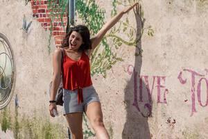 Festivalbesucherin posiert für Foto vor kunstvoller Wand am Tomorrowland Festival 2019 in Belgien