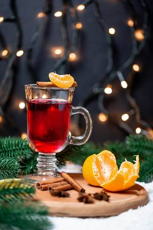 Festive mood with a warm Christmas drink: mulled wine with tangerine and cinnamon on a round wooden serving plate