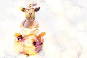 Festive winter background toy-deer on white snow with Golden bokeh background (Flip 2019)
