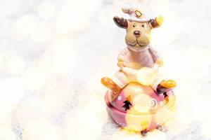 Festive winter background toy-deer on white snow with Golden bokeh background