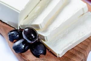 Feta cheese with olives on wooden board