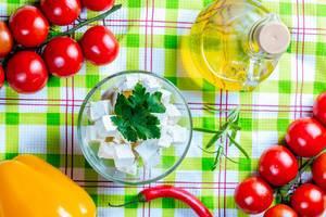 Fetakäse mit Petersilie, Paprika, Chilis, Tomaten, Karaffe Olivenöl und Rosmarin auf grünem Tuch