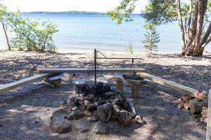 Feuerstelle mit Natursteinen und einfachen Holzbänken auf dem Eiland Kelvenne, einer Insel am Päijänne See in Finnland