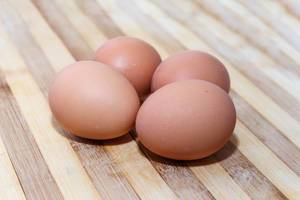 Few eggs on wooden background
