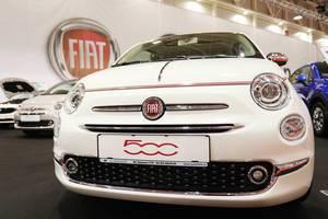 Fiat 500 in Weiß, Aufnahme von vorne mit großem Fiat Logo im Hintergrund