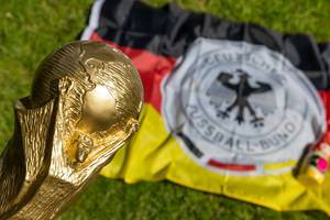 FIFA World Cup Trophy and German flag with emblem of the German football federation
