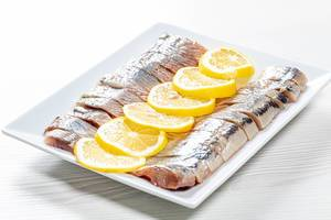 Fillet pieces salted herring with lemon