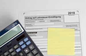 Finanzamt Formular: Leerer Antrag auf Lohnsteuerermäßigung unter gelbem Notizzettel und elektronischen Taschenrechner - Draufsicht