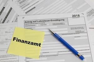 Finanzamt Schriftzug auf einem Post-It mit Kugelschreiber auf einem Lohnsteuer-Ermäßigungsformular