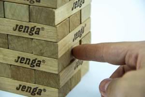 Finger schiebt einen Block aus einem Turm aus Jenga-Spielklötzen vor weißem Hintergrund