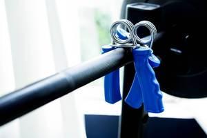 Fingerhanteln hängen auf einer Hantelstange im Fitnessstudio