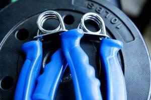 Fingerhanteln mit blauem Griff im Fitness-Studio
