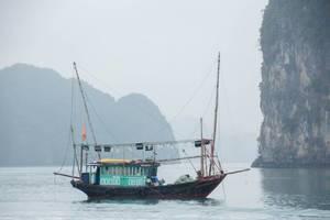 Fischerboot aus Holz auf See von hohen Felswänden umgeben
