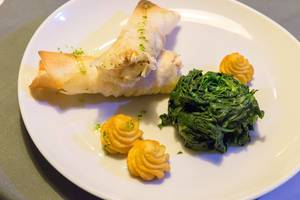 Fischröllchen mit Duchesse Kartoffeln und Spinat auf weißem Teller