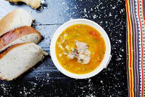 Fischsuppe mit hausgemachtem Brot serviert. Aufnahme von oben mit schwarzem Hintergrund