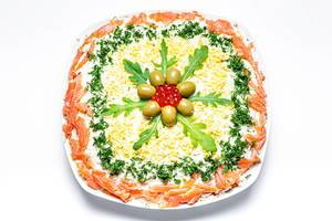 Fish and vegetable salad decorated with fresh herbs, olives and caviar. Top view (Flip 2020)