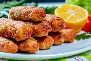 Fish cutlets fried on a plate with lemon