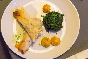 Fish rolls with duchess potatoes and spinach on white plate