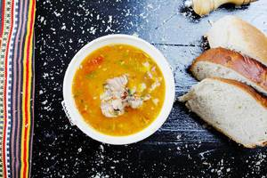 Fish soup served with homemade bread, black background (Flip 2019)