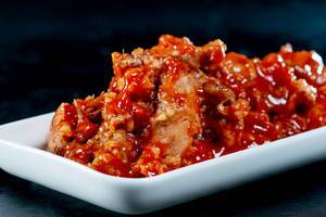 Fish with tomato sauce on a white plate