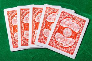 Five cards are laid out on a green background to start the game. The concept of gambling